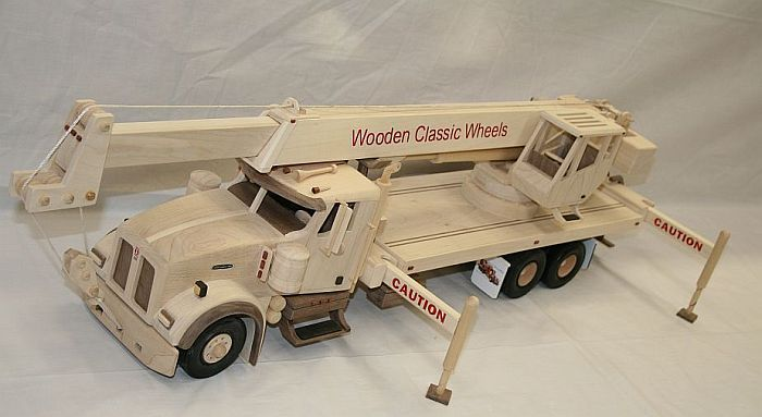 "KW Crane Truck   # 3420  Construction truck crane, boom will extend to over 40"" and rear crane boom will raise and lower and turn 360, rubber mud flaps  the outriggers move up , down and in , out. Let everyone see your pride by putting your logo all over it.  Built from: solid hard maple, black walnut, blood wood and black ebony w / painted black wheels  approx. size 32"" Long X 13"" Tall X 8"" Wide"