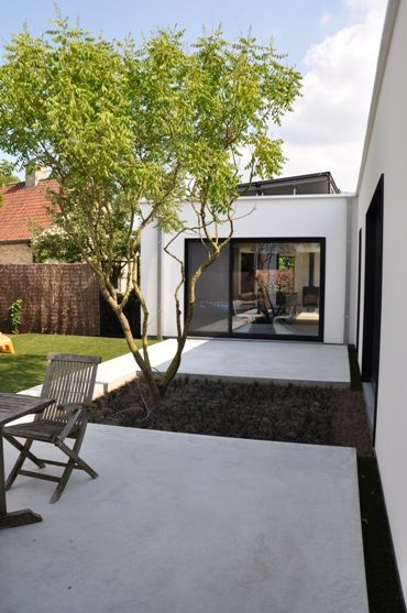 Courtyard/white stucco/black frame windows GEPOLIERD BETON