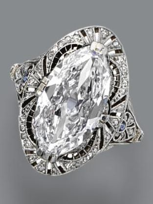 Diamond ring, circa 1915. The marquise-shaped diamond weighing 3.71 carats, in a pierced frame of conforming shape decorated with small single-cut diamonds and calibré-cut simulated sapphires, mounted in platinum.