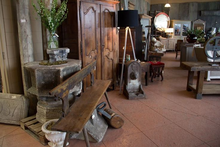 Ancient stone font from the UK, antique painted bench, vintage English tripod floor lamp.