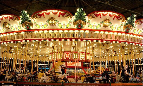 "The 1921 C.W. Parker Carousel by Cindirelli.    The C.W. Parker Carousel (or Jantzen Beach Carousel as it is often known) consists of 72 different ""jumper"" horses (with more horses in storage) at four rows across. It is lit by an amazing 1,350 lights and consists of 286 mirrors. The base is a large 67-foot diameter that can travel up to ten miles an hour on the outside steeds, making it the largest and fastest ride still in operation. Interestingly enough, the hand-carved horses are worth…"