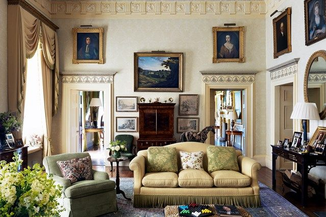 The morning room of Ugbrooke Park sees a sofa and armchair positioned around an ottoman topped with a leopard-print rug.