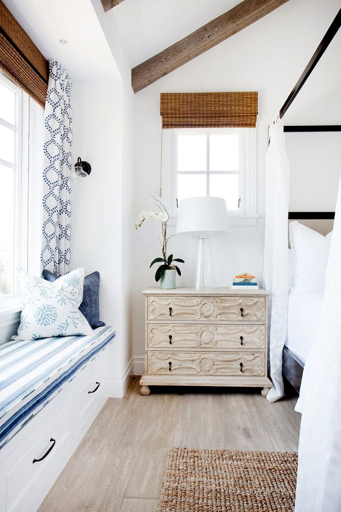 Bedroom with white walls, wood floors, brown rug, light wood bedside table, glass lamp, flowers, patterned blue and white bench and throw pillows, blue and white patterned curtain, and white bedding