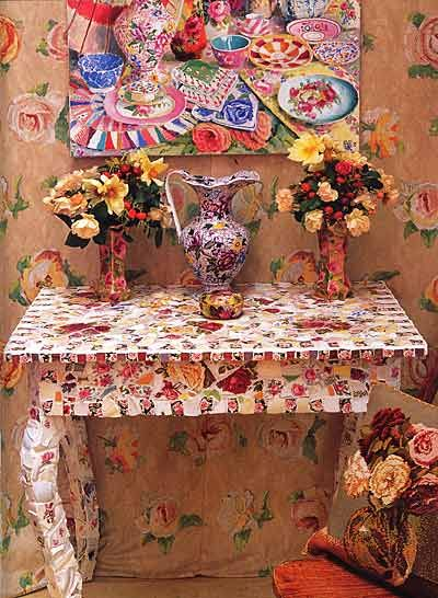 Kaffe Fassett: mosaic table with mosaic pitcher and vases with mosaic piece over them.