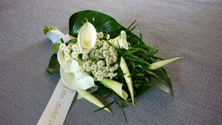 Funeral arrangement in teardrop shape - ornamental leaves with calla, anthurium and buttons chrysanthemum