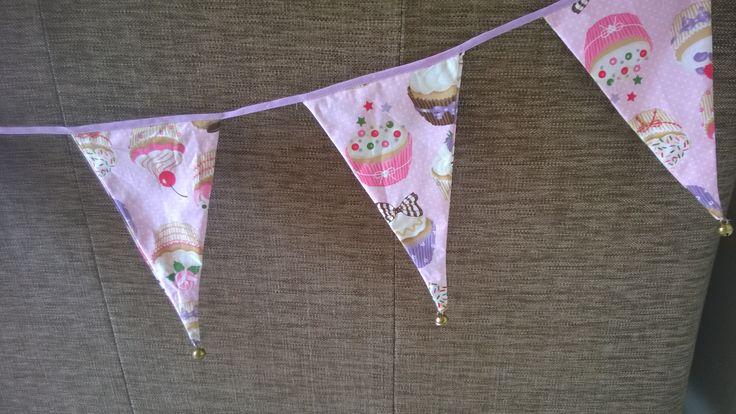 zelf gemaakte vlaggenlijn met cupcakes  onder aan de vlaggen hangt een belletje