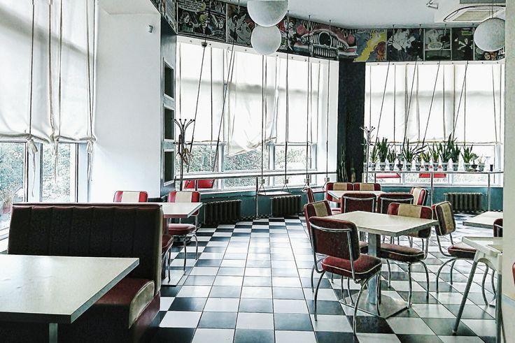 Помещение кафе бара, большие витринные окна, качели, пол плитка в шахматном порядке, белая и черная, яркие малиновые стулья и бирюзовый стены.