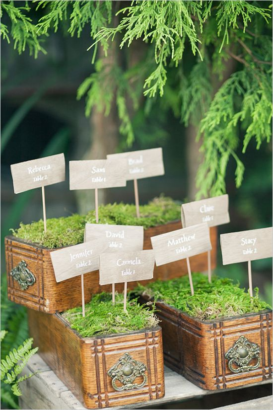 Vintage sewing drawers + moss make a lovely escort card display.