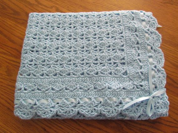 This is a beautiful afghan crocheted in an heirloom lace pattern with ribbon trim. Blue in color for a boy. A perfect addition to that special