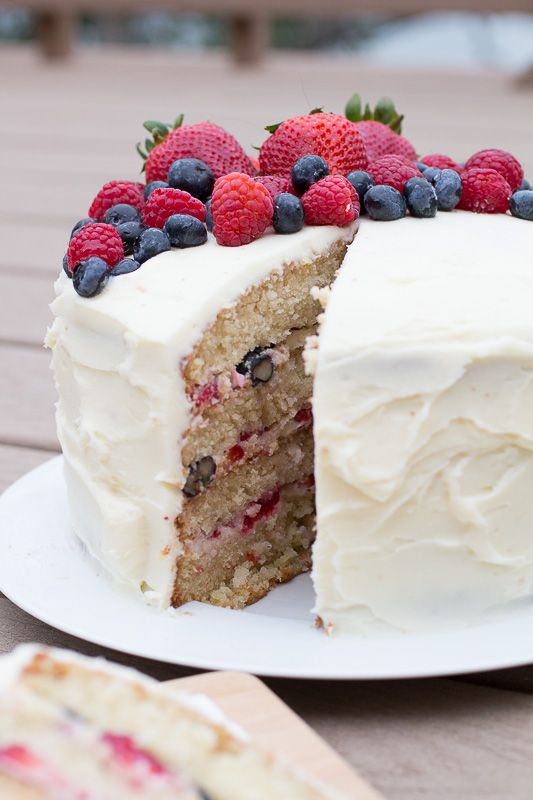 super moist yellow cake (made with butter, oil, and buttermilk) brushed in a berry jam simple syrup, filled with fresh berries, and frosted with a sweet, fluffy, whipped mascarpone cream cheese frosting