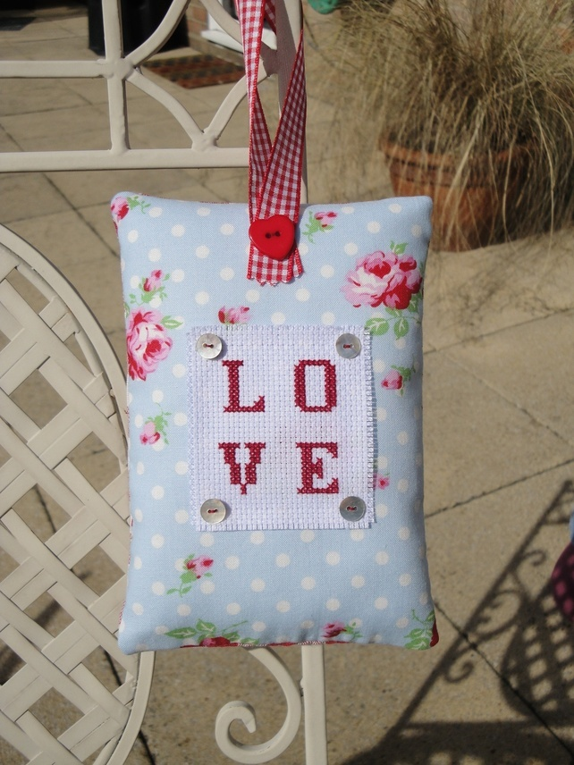 trimmed with a red checked ribbon and a red heart button. The Love motif in red cross stitch is embellished with tiny shell buttons.  backed with red gingham linen fabric.  filled with toy stuffing and measures 18cm by 13cm.