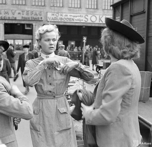 Member of Lotta Svärd putting ID card in her pocket while saying good byes to her relatives before starting her journey towards the eastern border. Helsinki, 20 June 1941.