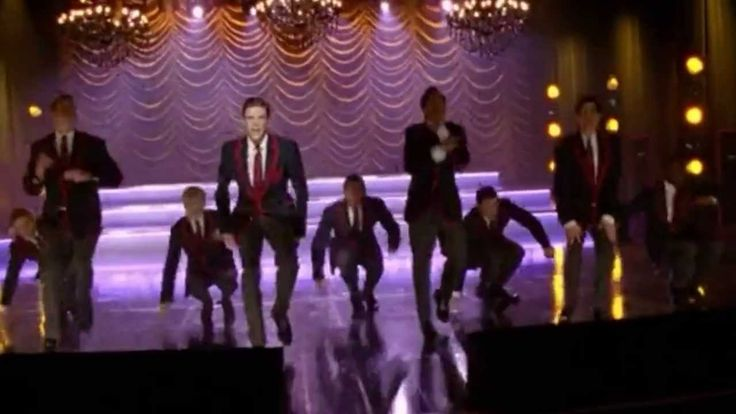 "GLEE - Live While We're Young (Full Performance) (Official Music Video) HD -  Sung by: Sebastian Smythe/Grant Gustin with The Warblers. Episode: 4x08 ""Thanksgiving""."