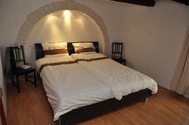 hoofdeinde van het bed in de muur weggewerkt, met verlichting.