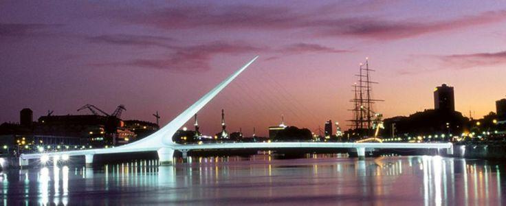 Puente de la Mujer, peatonal, largo 170m y ancho 6,2m, con dos secciones fijas laterales de 25m y 32,5m y una móvil central colgante y rotatoria de 102,5m sobre pilón cónico de hormigón, sostenida por una aguja inclinada a 39º de acero con alma de cemento de 34m, de la cual penden los cables. Arquitecto Santiago Calatrava. Fabricado en Vitoria (España) e inaugurado en 2001 en Dique 3 de Puerto Madero, Ciudad de Buenos Aires. El diseño es una síntesis de la imagen de una pareja bailando tango