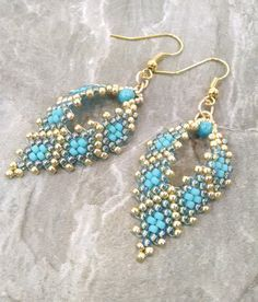 """The earrings are already made and ready to ship. Opalescent teal, matte teal, and metallic gold colored Japanese glass seed beads are hand stitched together using the peyote technique creating a leaf shape. SIZE: The beaded portion of the earring is approximately 1 1/2"""" long. The total length of the earring is 2 1/2"""" from the curve in the earring wire down to the very bottom tip. These earrings are very lightweight. Use this link to see more earrings at Alleyway Beading: https://www.etsy..."""