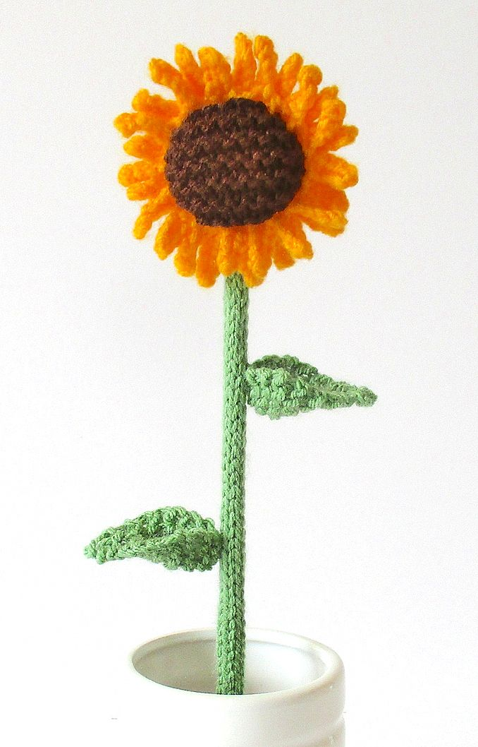 Free Knitting Pattern for Sunflower - Designed by Amanda Berry,  all pieces are knitted flat (back and forth) on a pair of straight knitting needles, apart from the stalk which is i-cord knitted on two DPNs. The sunflower is approximately 7cm diameter, and the flower and stalk are 21cm tall. DK yarn. You can make and sell for charity.