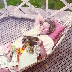 Marimekko's founder, Armi Ratia, reading on her hammock, circa 1960.