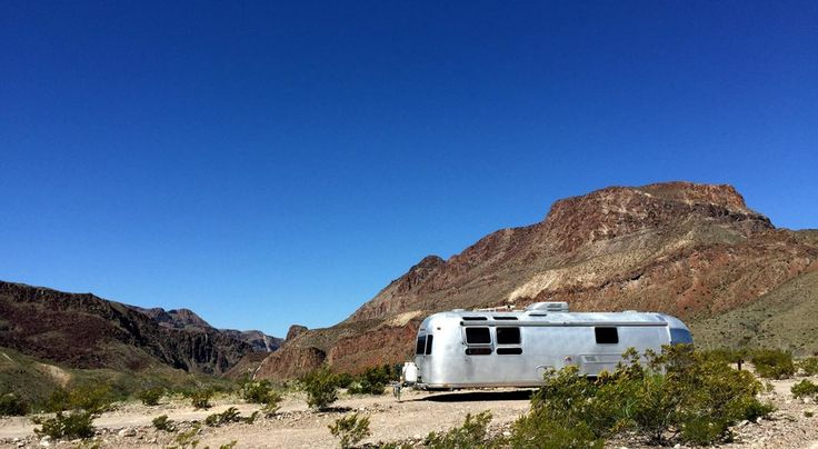 a vintage 1976 airstream travel trailer at big bend ranch state park, surrounded by blue skies and big mountains