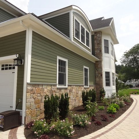Combining colonial tan natural stone with olive green for Sustainable siding