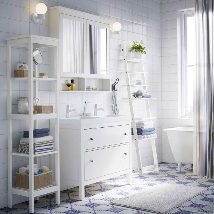 Baño blanco con armario para lavabo, estante y armario de espejo HEMNES blancos, cortina de ducha azul y toallas azules y blancas.