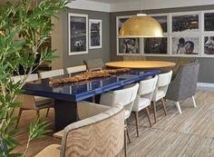 O ponto vibrante pode morar até na mesa de jantar. Foi a ideia de Rafael Souza e Jorge Trabuco na Sala de Jantar Contemporânea para a Decora Lider Salvador. O azul intenso, de acabamento laqueado, sobressai em meio ao branco, cinza e madeirados do piso e do resto dos móveis. A parede cinza, com fotos em P&B, não deixa pesar o visual. Para arrematar, o toque glamoroso do pendente dourado.