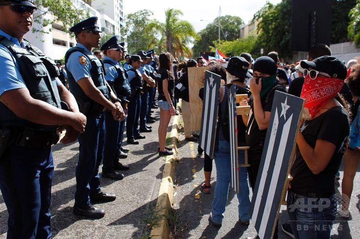 米自治領プエルトリコの首都サンフアン San Juan で、米国の51番目の州への昇格案の是非を問う住民投票に抗議するデモ隊と相対する警官隊(2017年6月11日撮影)。(c)AFP/Ricardo ARDUENGO ▼12Jun2017AFP|米領プエルトリコ住民投票、「51番目の州」昇格を97%が支持 http://www.afpbb.com/articles/-/3131665