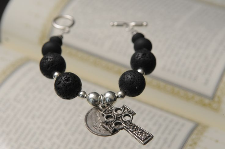 Bracelet made with black volcanic stone beads, coin + cross. By Tinky. https://www.facebook.com/TinkySonntag