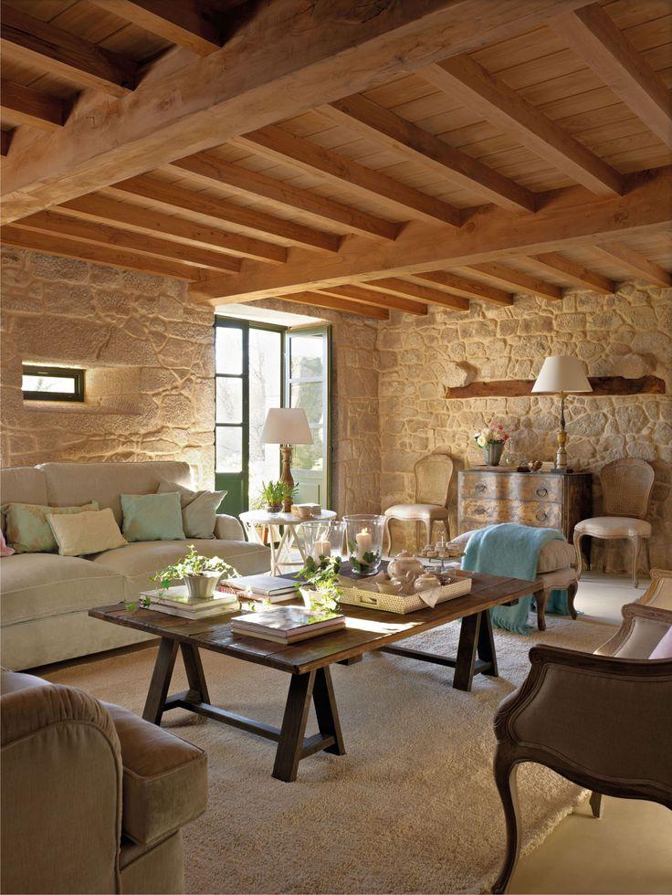 Salón con vigas de madera y muros de piedra con una mesa de centro de madera oscura_00315360