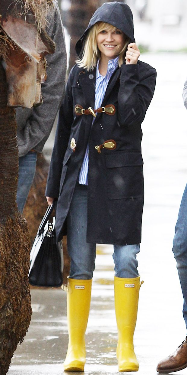 Reese Witherspoon sports a Michael Kors coat, Saint Laurent Sac de Jour bag, and bright yellow Hunter Original Boots for perfect rainy day style: