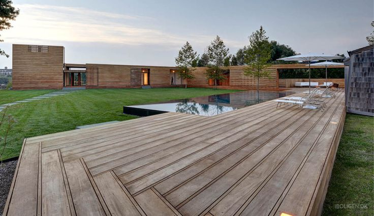 Luksus sommerhus i træ med terrasser og pool i midten