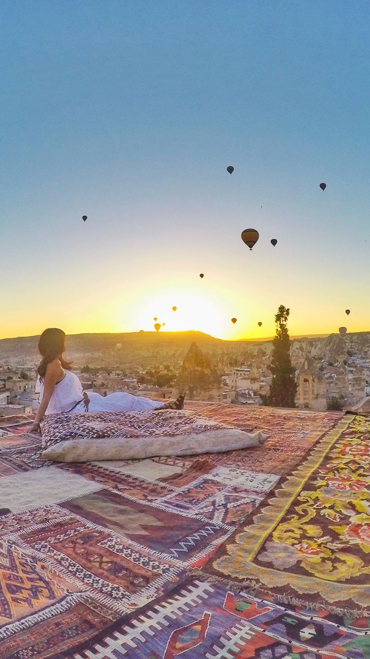 Sunrise in Cappadocia (Turkey) with hot air balloons. This is Sultant cave suites in Göreme.. magic carpet carpet ride with hundreds of hot air balloons in the background. Goreme, Cappadocia, Turkey.
