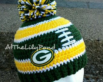 """This adorable Green Bay Packers hat is made with a soft, 100% acrylic yarn with crochet flower with pearl securely attached. This hat is perfect for accessorizing, as a photo prop, and for keeping your little one's head warm while supporting your team!  All of my products are made in a clean, smoke, and pet free environment.  All items are made to order unless marked as """"READY TO SHIP"""" in the title.   My sizes are approximate and all my products have a little stretch to them. I have…"""
