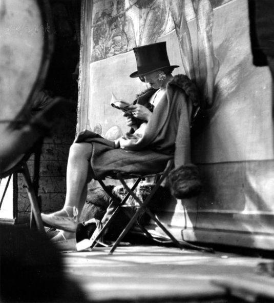 Carnival, (woman reading behind stage), Paris, 1926  by André Kertész