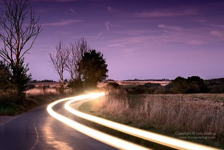 Light trails at dusk on a country road near Kersey village in Suffolk, england,uk