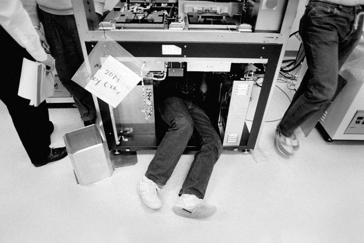 """Unknown Unknowns. Fremont, California. 1990. Menuez: """"An engineer at Lam Research labors to solve an electrical connection problem in the assembly of a sophisticated plasma etching tool.""""DOUG MENUEZ"""