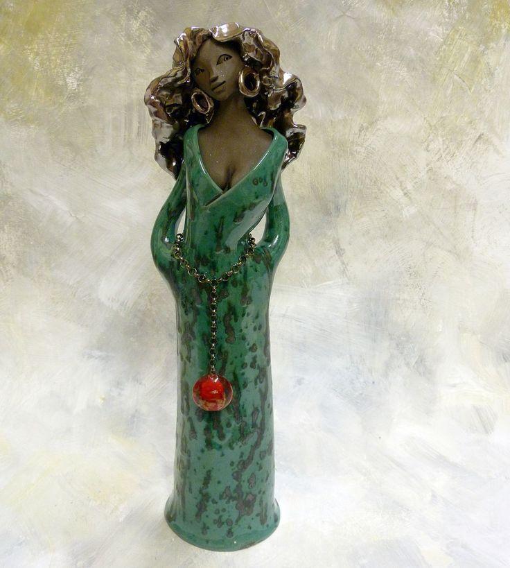 Margarena - černá kráska s dlouhými vlasy Soška je vyrobena z velmi tmavé hlíny. Má dlouhé vlasy ozdobené kovově lesklou glazurou. Šaty jsou glazovány glazurou v sytě smaragdově zelené barvě s rozpitými tmavými skvrnkami. Na nich se velmi vyjímá rudá vinutka, zavěšená na řetízkovém opasku. Výška sošky je cca 38cm.