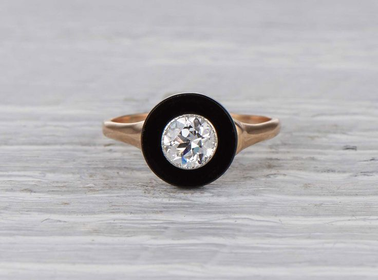 Vintage Art Deco engagement ring made in 14k yellow gold and centered with an approximate .55 carat EGL certified old European cut diamond with F-G color and SI1 clarity. Accented with onyx. Circa 1925