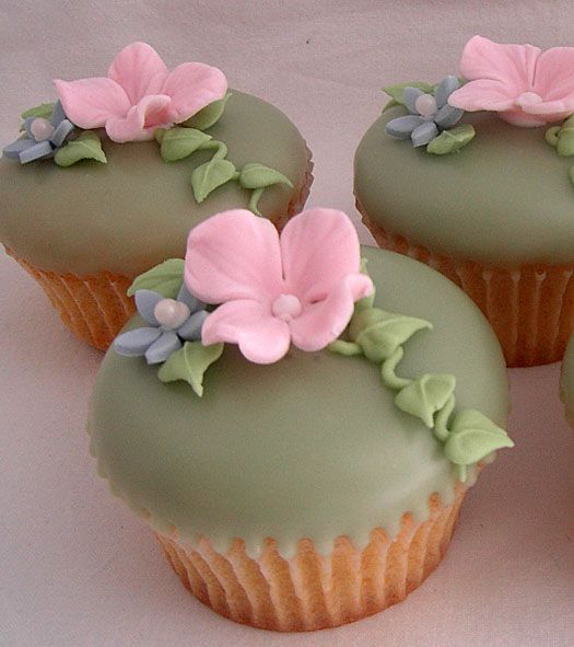How to make poured fondant icing | Cupcake decorated with green poureable fondant with royal icing flowers and trailing vines.