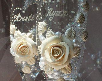 Twee zeer zachte witte bruiloft of verjaardag champagne glazen ingericht met handgemaakte originele design met parels, kristallen kralen en handgemaakte duiven en rozen (met glans effect polymeerklei). Kristal kralen geeft een mooie glans effect, helaas fotos niet kunnen overbrengen. Zij zullen een prachtige decoratie voor uw huwelijk. Het kan zijn een geweldig cadeau voor elke gelegenheid voor u of voor uw vrienden.  Hoogte van de bril 8,5  PERSONALISEREN Zowel namen en datum kunnen worden…
