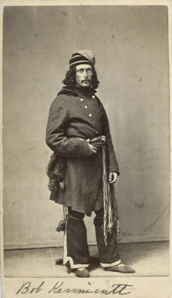 Robert Kennicott, American Naturalist: Portage La Loche, 1862: Wearing a double breasted capote, a knee length wool jacket with hood, tied at the waist with an Assomption / Metis sash and a marten fur skin fire-bag; pants are trimmed with ribbon on the outside seams and on cuffs; wearing a toque; pants tied just below the knee with garters ending in tassels. On his feet are beaded or embroidered moccasins; clothing type worn by French Canadians and French Canadian Metis of the North West
