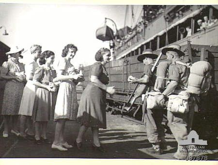 Townsville, Qld. 1945-03-25. Australian Comfort Fund workers greeting soldiers from the H.T. Katoomba with bags of fruit.