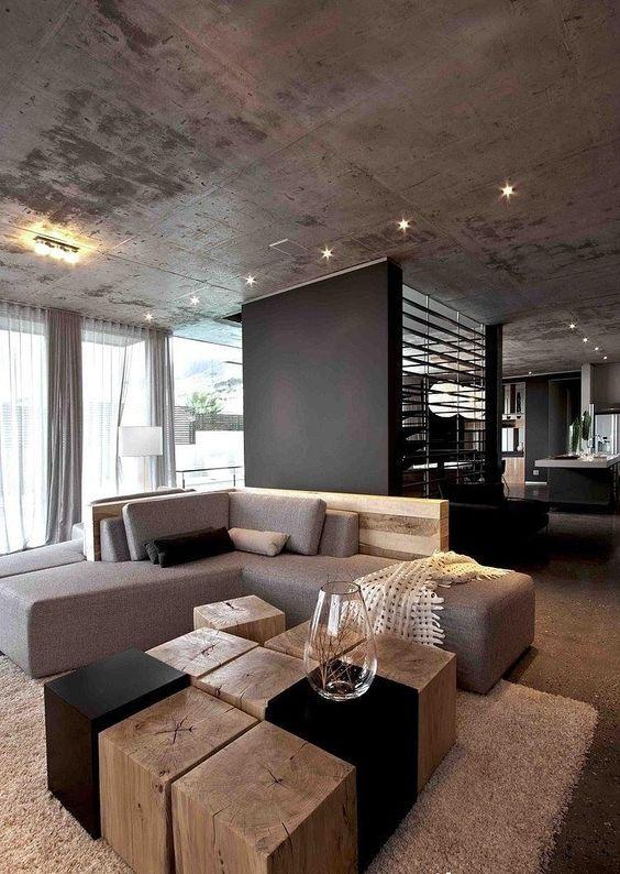 wohnzimmer-grau-eckcouch-baumstumpf-holzbloecke-couchtisch-betondecke-minimalistisch