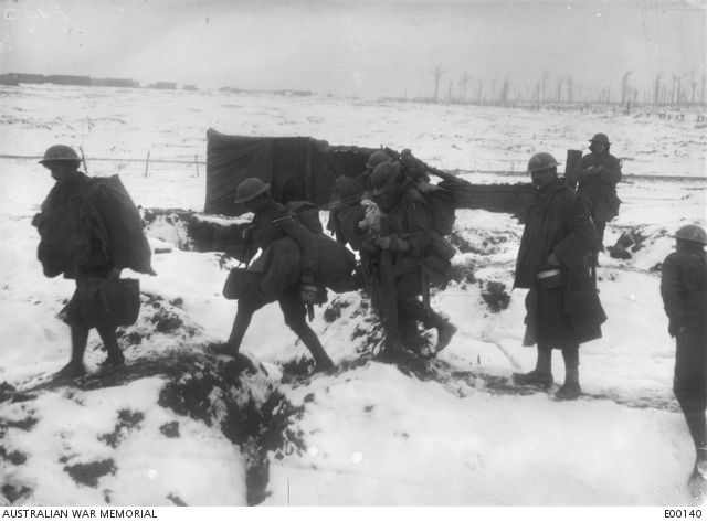 WWI, Jan 1917; Australians moving into reserve near Bernafay Terminus along a frozen track through the old trench system behind Delville Wood. -AWM