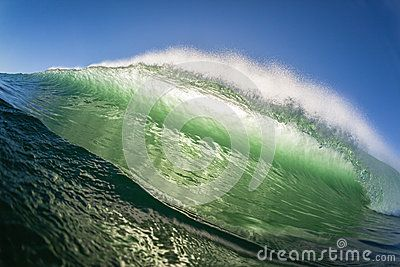 Ocean wave wall of rushing water crashing on shallow sandbars in morning back light color contrasts