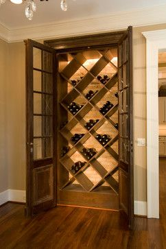 Traditional style home includes a Wine Storage Closet with antique French doors and reclaimed brick at back wall (image via Whitestone Builders)