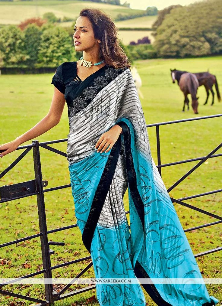 Blue and grey georgette saree is design with abstract prints swirl across the first and second halves of the saree. Stick on crystal foliage patch border enhances the demeanor. Comes with matching blo...
