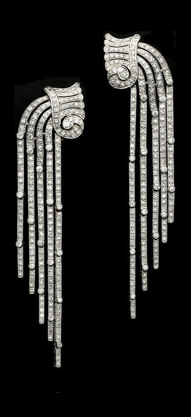 A stunning pair of Art Deco platinum and diamond earrings circa 1935. Designed as a cascading waterfall of diamonds, the tops modelled as stylised vessels with scrolled and fluted necks from which pour forth five articulated rows of round diamonds tapering to a point, with clip fittings. #ArtDeco