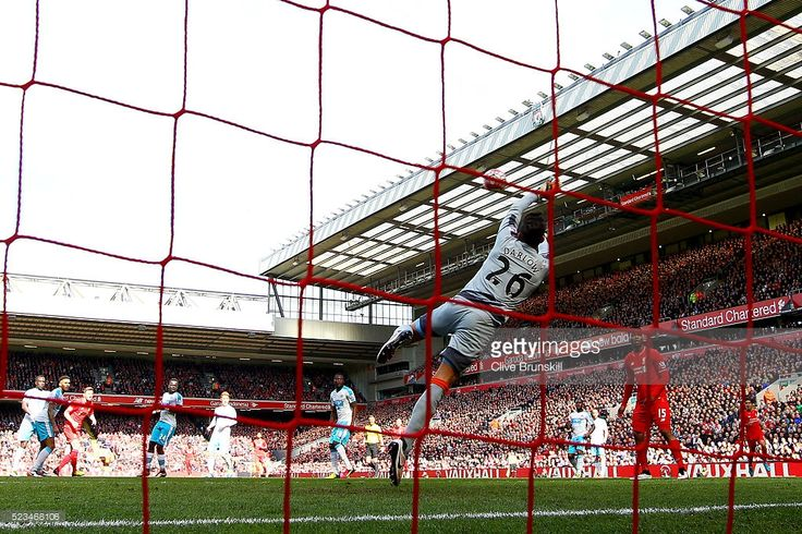 Adam Lallana of Liverpool places the ball past Karl Darlow of Newcastle United to score his sides second goal during the Barclays Premier League match between Liverpool and Newcastle United at Anfield on April 23, 2016 in Liverpool, United Kingdom.