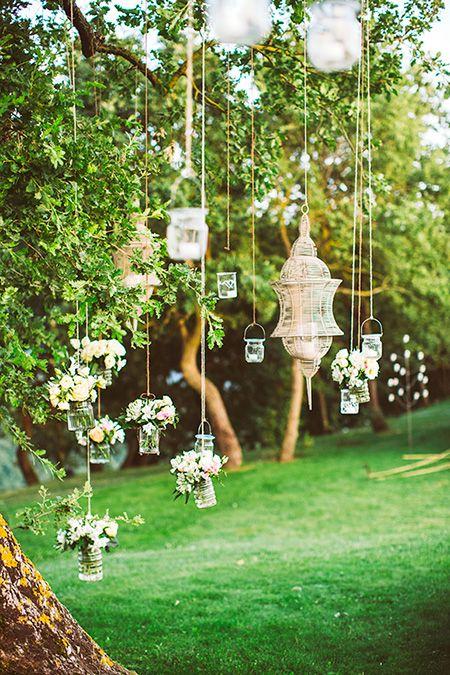 Decoración de boda en jardín con velas colgando